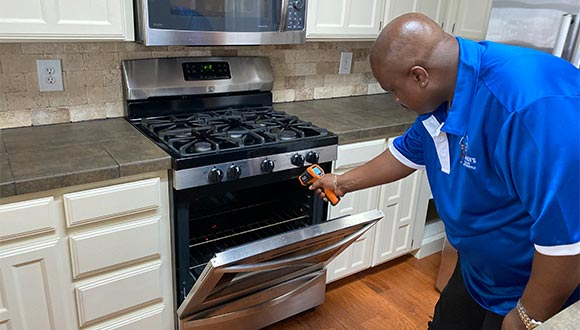 Stephen Hearn, professional home inspector in Little Elm Texas, checking the temperature inside a stove.