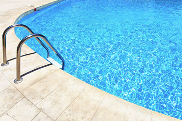 Allen, Texas — A ladder leading into a pool with clear blue water.