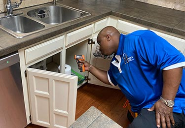 Melissa, Texas — Stephen Hearn, professional home inspector, checking the kitchen plumbing.